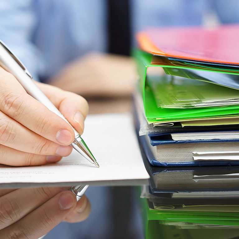 businessman is writing on document and a lot of documentation is